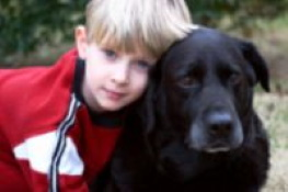 young boy with aging black dog